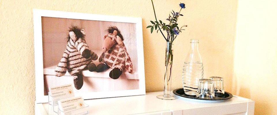 Praxisempfang mit Maskottchen Nasi und Zebri, Blumen und Wasser